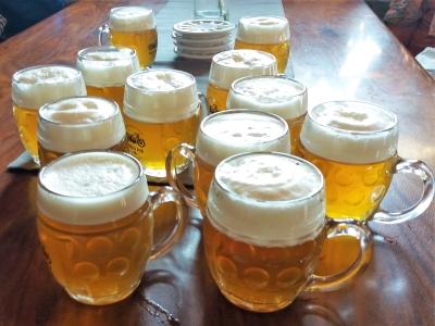 Wyjazd integracyjny na piwo i wino do Czech. Kufle z jasnym piwem na stole