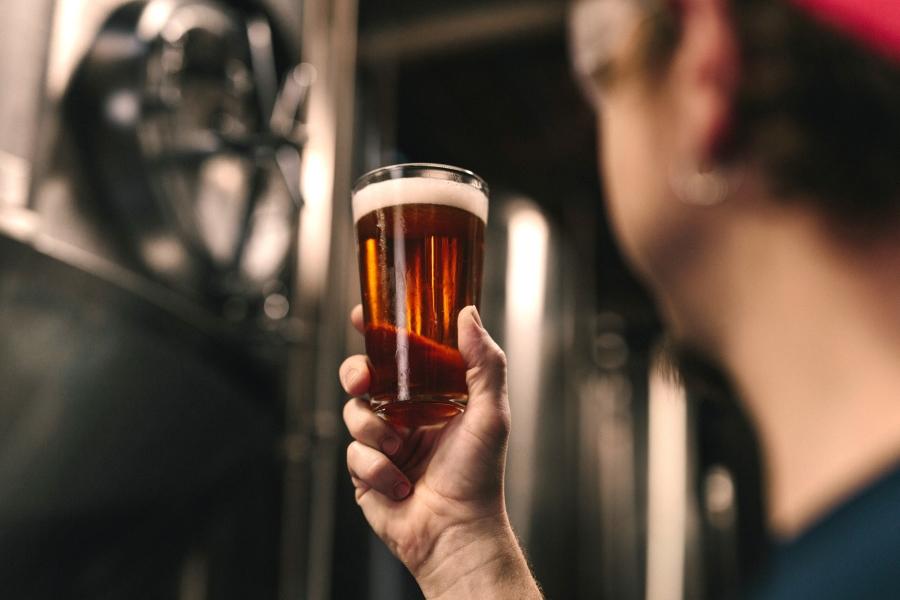 Wycieczki piwne. Piwowar z kuflem piwa.