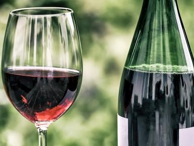 Wyjazd winiarski do Włoch. Butelka z lampką czerwonego wina